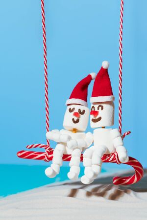 Two lovers of Marshmallow snowmen are sitting on a swing of candy. Christmas holidays on the beach.
