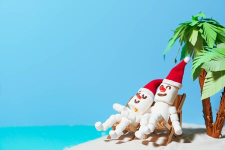 Two marshmallow snowmen in love are sitting on deckchairs on a sandy beach. Christmas holidays on the beach.