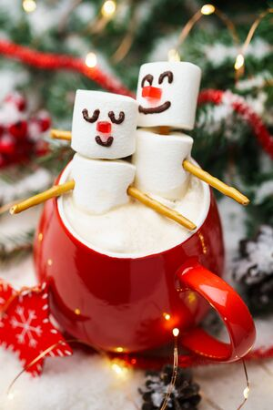 Red mug with hot chocolate and two marshmallows in love. Christmas meeting a couple in love concept.