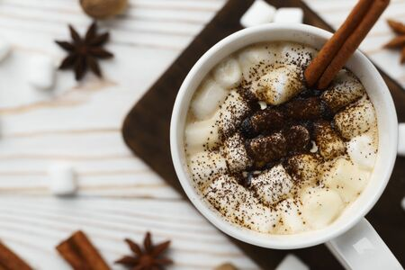 White mug with hot chocolate and marshmallows with cinnamon stick on a wooden table. Hot winter drink, top view. Stok Fotoğraf