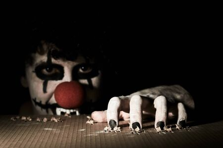A terrible creepy clown peeps out of the basement and scratches the floor with his claws. Reklamní fotografie