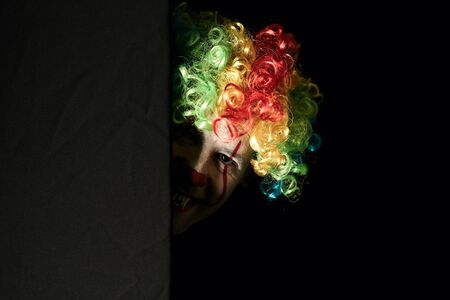 Close-up of a scary clown peeping around the corner of a black wall. He is wearing a colored wig and sharp fangs. Reklamní fotografie - 135483584