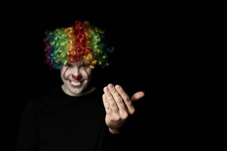 A creepy clown in a colored wig calls for himself with a hand gesture. Stands in a dark room and smiles. Empty space on the right Reklamní fotografie - 135483596