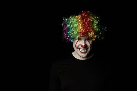 Creepy clown in a colored wig and sharp fangs in a dark room. The empty space on the left.