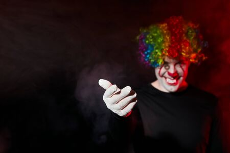 A creepy clown in a colored wig smiles and beckons to himself with a gesture of his hand. Stands in a smoky dark room. Reklamní fotografie - 135483587