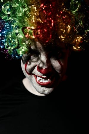 Portrait of an evil creepy clown. Man in clown makeup for Halloween holiday.