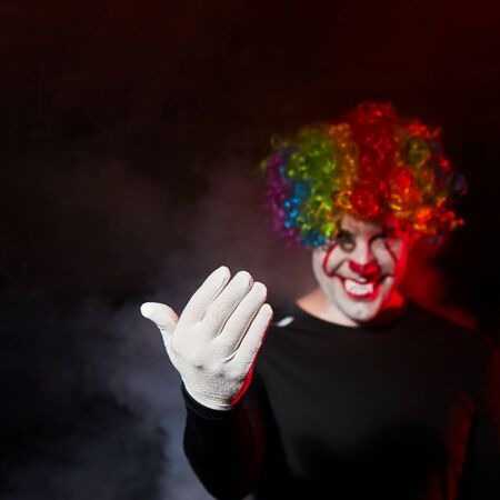 A creepy clown in a colored wig smiles and beckons to himself with a gesture of his hand. Stands in a smoky dark room. Reklamní fotografie - 135483591