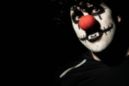 Blurred portrait of a scary clown in a black wig and makeup. A man in a costume of a creepy clown with a red nose. Reklamní fotografie - 135483603