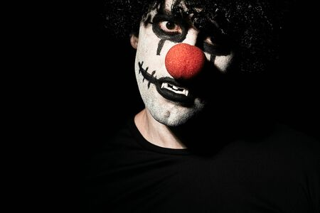 Close up portrait of a scary clown in a black wig and makeup. A man in a costume of a creepy clown with a red nose. Banque d'images