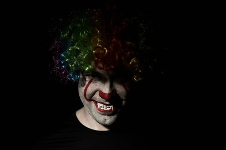 Close-up of a creepy clown peeping out of the darkness. He is wearing a colored wig and sharp fangs. Reklamní fotografie - 135483565
