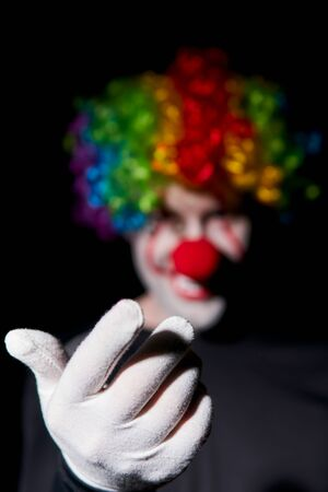 A creepy clown in a colored wig smiles and beckons to himself with a gesture of his hand. Stands in a smoky dark room.