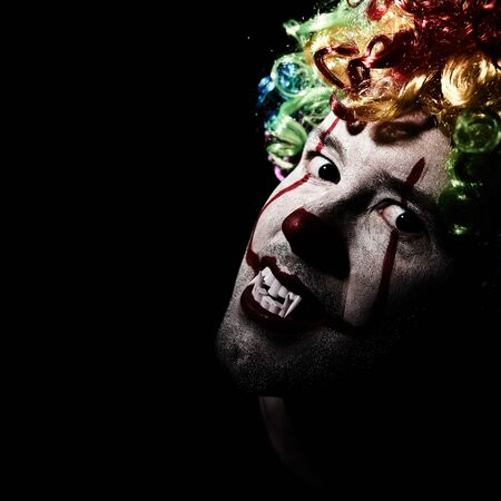 Closeup portrait of a creepy clown in a colored wig. Black blank space on the left Reklamní fotografie