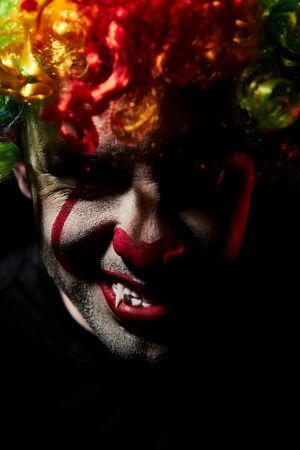 Angry scary clown grimacing showing fangs. Closeup portrait wearing a colored wig with creepy red eyes Reklamní fotografie - 135483571