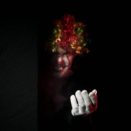A creepy clown in a colored wig looks around the corner and beckons to himself with a gesture of his hand. Stands in a dark room and smiles. Reklamní fotografie - 135483575
