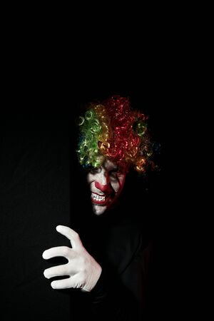 Scary clown peeping around the corner of a black wall. He is wearing a colored wig and sharp fangs. Reklamní fotografie - 135483576