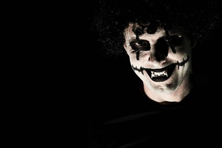The terrible creepy clown in a black wig grins, looking at the camera. Empty space on the left, black background. Reklamní fotografie