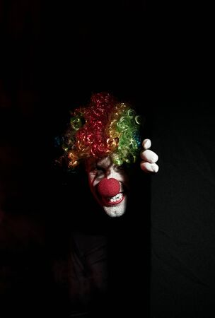 Scary clown peeping around the corner of a black wall. He is wearing a colored wig and sharp fangs. Reklamní fotografie - 135483540