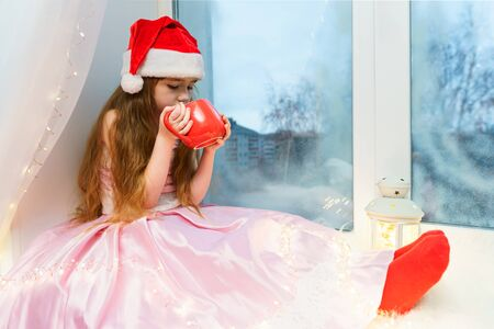 Cute little girl in a pink dress and santa hat sits on a windowsill with a red mug of hot chocolate in her hands.