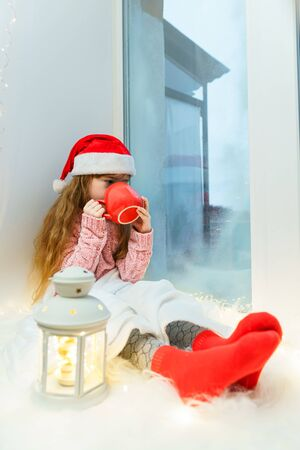 Cute little girl in a pink sweater and santa hat sits on a windowsill with a red mug of hot chocolate in her hands. Zdjęcie Seryjne