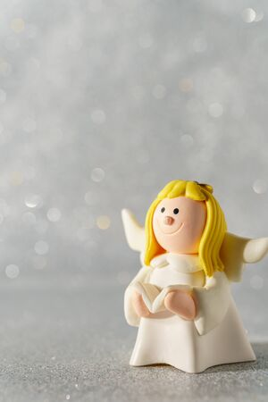 Angel figurine on a beautiful bokeh background with empty space for text.