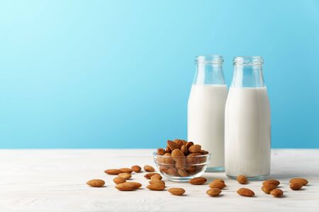 Two glass reusable bottles with almond milk. Almond nuts lie on a white wooden table and a blue background.