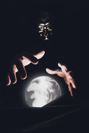 A clairvoyant man in a mask of a skull holds his hands over a magic crystal ball.