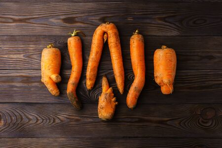 A few ugly carrots in the center of a dark wooden table. Horizontal orientation, top view.