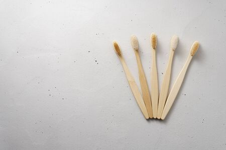 Five bamboo toothbrushes on a light gray concrete background. Top view with copy space. Zero waste and no plastic concept. Biodegradable personal care products. Reklamní fotografie
