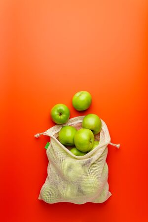 Green apples in a mesh grocery bag on a red background. Flat lay, copy space. Zero waste and no plastic concept.