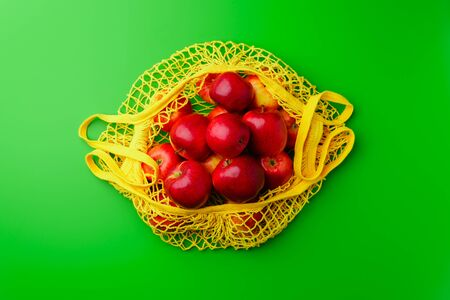 Yellow string bag with red apples on a green background. Flat lay, copy space. Zero waste and no plastic concept.