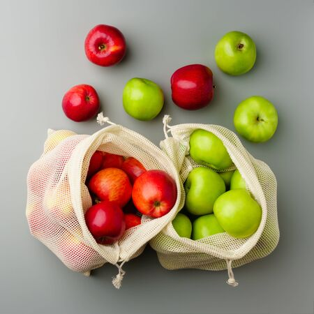 Red and green apples in mesh grocery bags on a gray background, top view. Zero waste and no plastic concept.