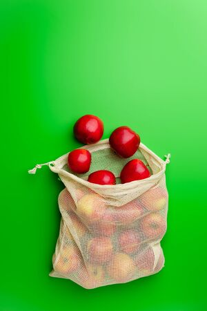 Grocery cotton net bag with red apples on a green background. Flat lay, copy space. Zero waste and no plastic concept.