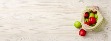 Biodegradable cotton grocery bag with red and green apples on a white wooden background. Horizontal orientation with copy space, banner. Zero waste and no plastic concept.