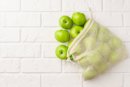 Biodegradable cotton bag with green apples on a white brick background. Horizontal orientation with copy space. Zero waste and no plastic concept.