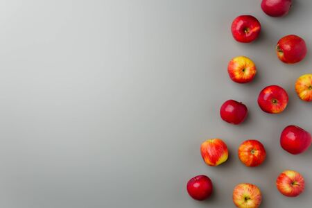 Groups red apples on a gray background. Flat lay, copy space.