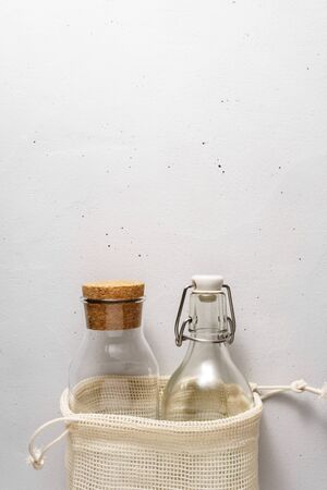 Cotton bag and glass bottles on a light gray concrete background. Top view with copy space. Zero waste and no plastic concept.