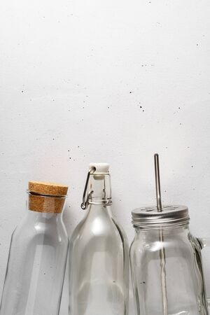 Three glass bottles on a light gray concrete background. Top view with copy space. Zero waste and no plastic concept.
