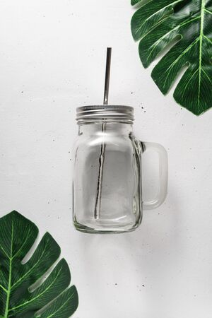 Glass jar with a metal cocktail straw on a light gray concrete background. Top view with copy space. Zero waste and no plastic concept. Reklamní fotografie