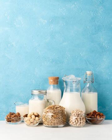 Different types of lactose-free vegetarian dairy products. Milk from macadamia, chickpeas, oats, walnuts and almonds on a pastel light blue background. Proper nutrition concept. Copy space.