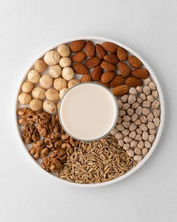 A set of macadamia nuts, walnuts, almonds, chickpeas, oats grains on a flat plate and in the center is a glass cup with milk. Dairy-free milk concept, vegan food. Top view. Reklamní fotografie