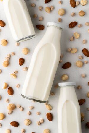 Three glass bottles with milk and scattered macadamia nuts, almonds, chickpeas on a light gray concrete surface. Dairy-free milk concept, vegan food. Top view, close-up.