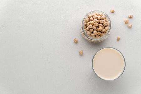 Milk in a glass of chickpea and beans in a jar on a light gray concrete background. Top view, copy space. No lactose concept, vegan food.