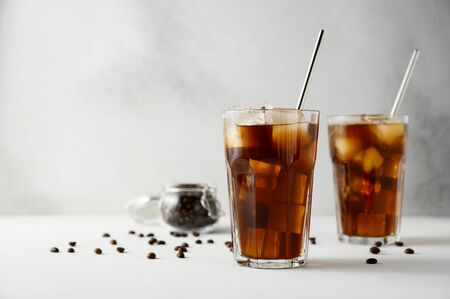 Two glasses of iced coffee and metal straws on a concrete table. Iced coffee on a light background. Copy space, horizontal orientation.