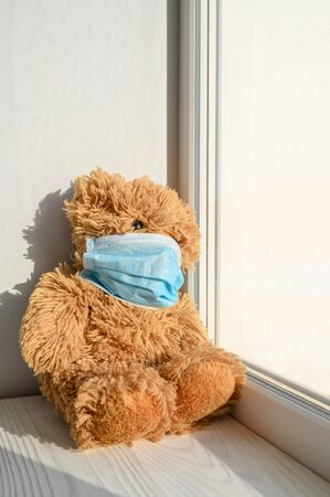 A teddy bear in a medical protective mask sits on a windowsill and looks out the window. Sadness and loneliness during quarantine at home. Vertical orientation.