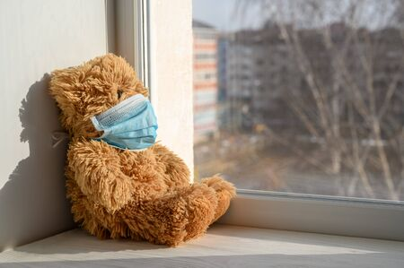 A teddy bear in a medical protective mask sits on a windowsill and looks out the window. Sadness and loneliness during quarantine at home. Copy space, horizontal orientation. Reklamní fotografie