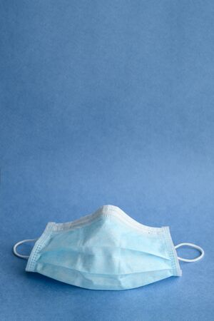 Medical surgical mask on a blue background. Face mask to protect the mouth and nose. Copy space. Coronavirus protection concept.