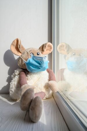 A plush toy rat in a medical protective mask sits on a windowsill and looks out into the street. Sadness and loneliness during quarantine at home. Symbol of 2020. Vertical orientation. Reklamní fotografie