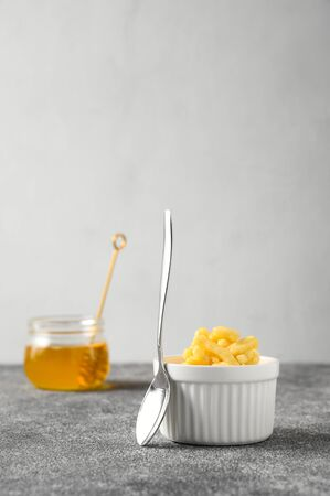 National food cuisine of the Middle East. Sweet dessert made of dough and honey chak-chak in a ceramic white bowl and a teaspoon on a gray concrete table. Vertical orientation, copy space. Reklamní fotografie