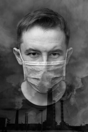 Double exposure portrait of an adult man in a protective mask and industrial exhaust pipes with smoke. Air pollution concept. Black and white image, vertical orientation. 版權商用圖片