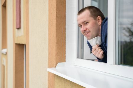 Caucasian adult man smiles, looks out of apartment window and takes off protective mask. End of quarantine, self-isolation and the COVID-19 pandemic. Horizontal orientation, copy space.